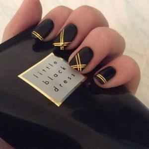 uñas negras con rayas doradas